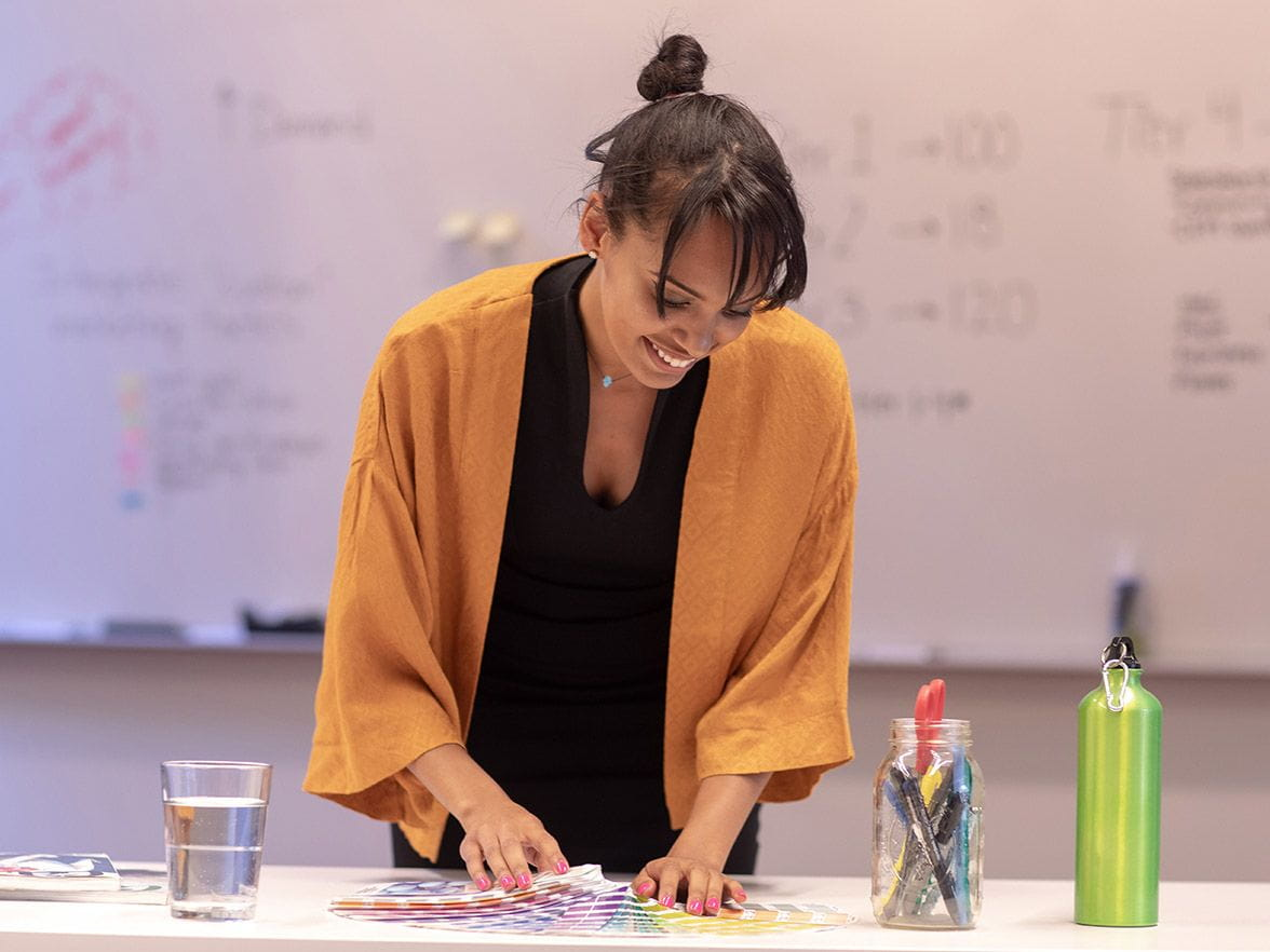 Teacher smiles and looks down in front of white board | Bright Horizons