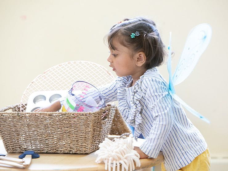 little girl with toy fairy wings looking in a basket