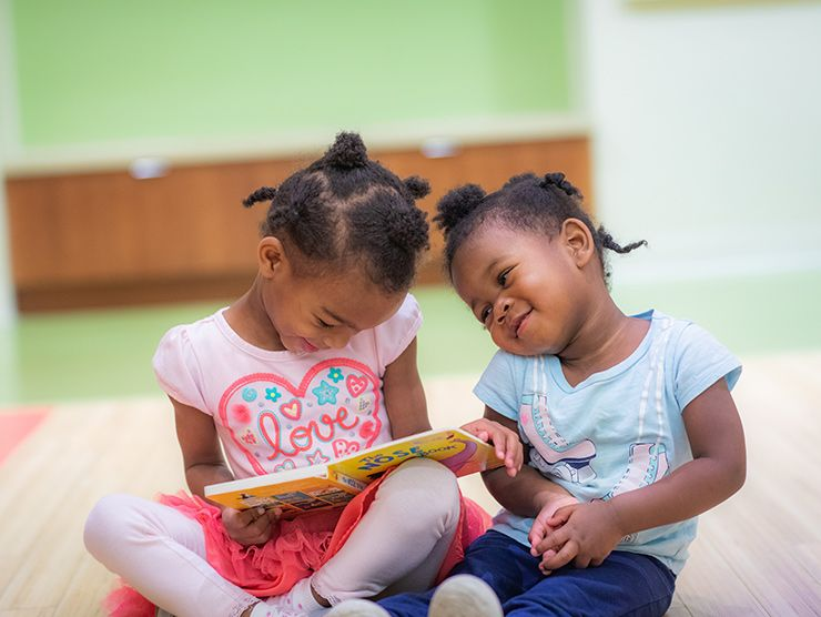 sisters reading a book happy