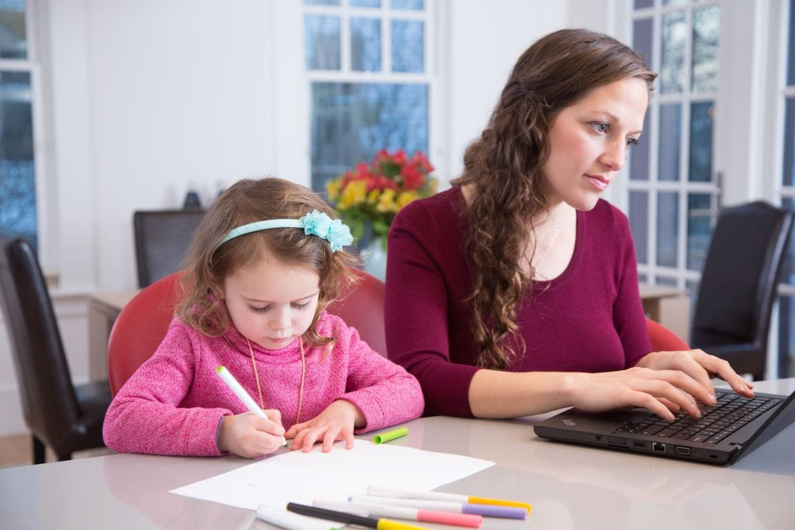 Mother working at home with child beside her