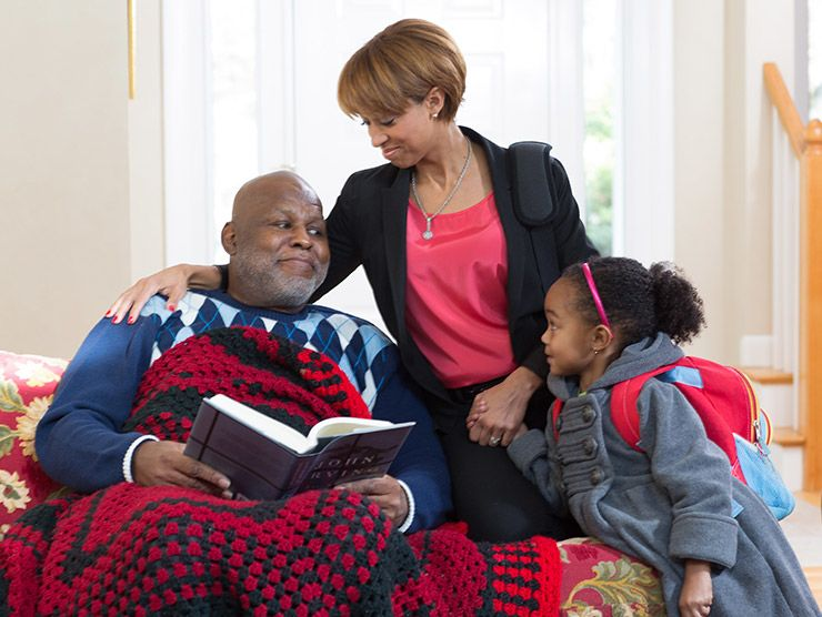 elder man reading on couch with family