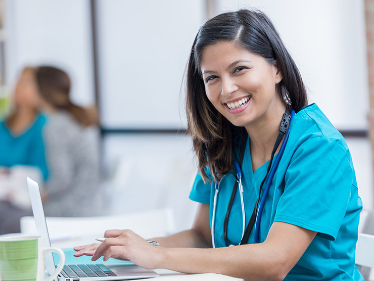 nurse smiling while on laptop