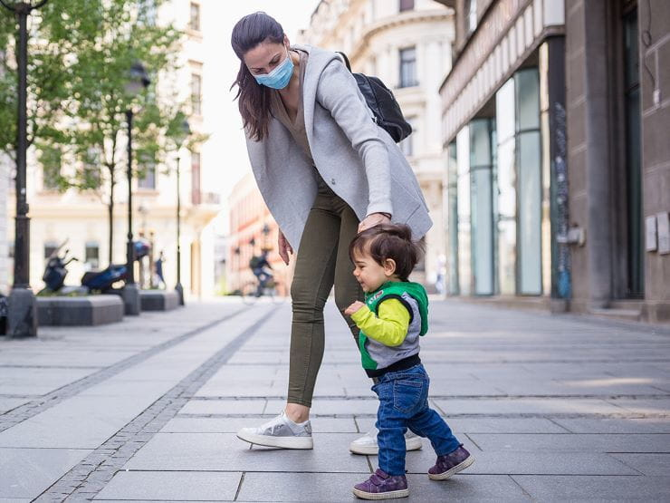 mother with her child on street wearing mask