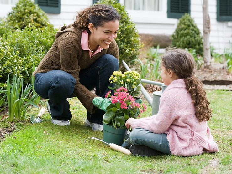 Mother smiling and playing with daughter in garden outside