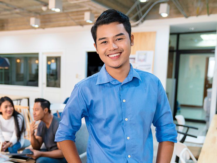 man in blue collard shirt smiling