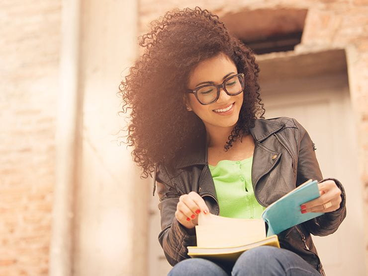 woman reading notes outside smiling