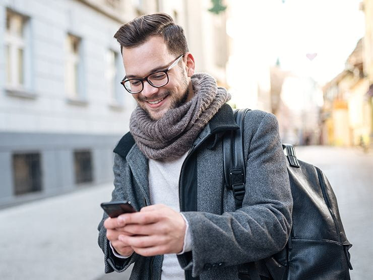 man smiling looking at phone