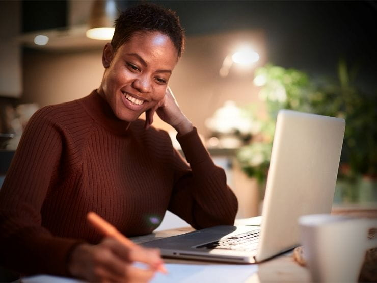 woman at her desk working on laptop and taking notes smiling