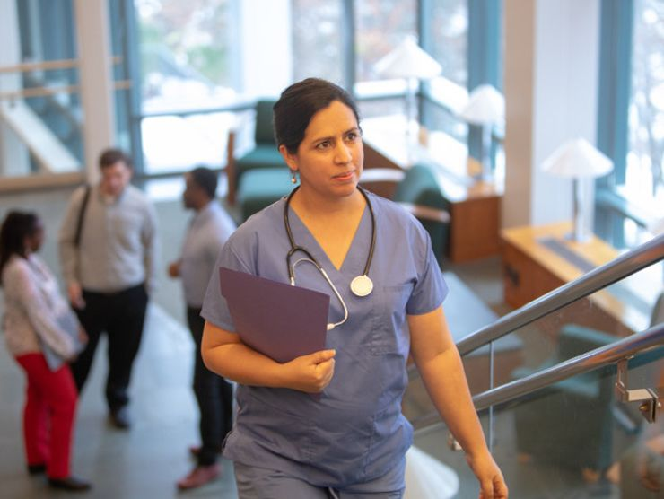 A nurse walking up stairs.