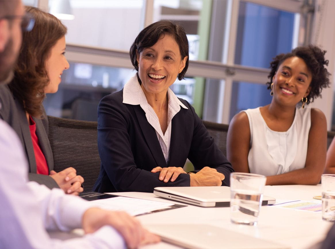 A group of women leaders at a conference table.