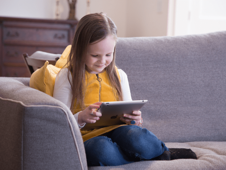 little girl reading tablet on couch