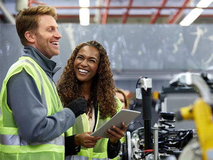 Male and female manufacturing workers conversing