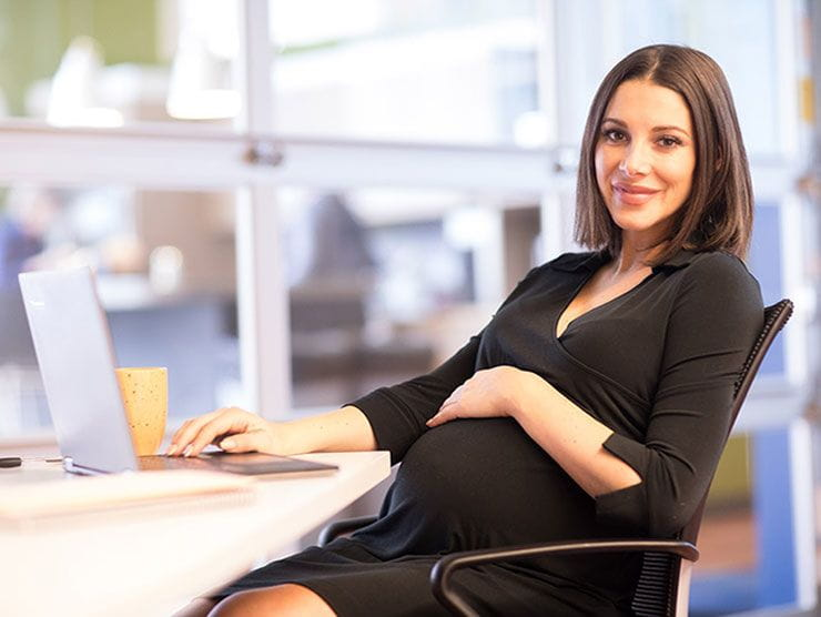 Pregnant CEO working on her laptop