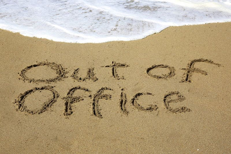 """Out of Office"" written in the sand"