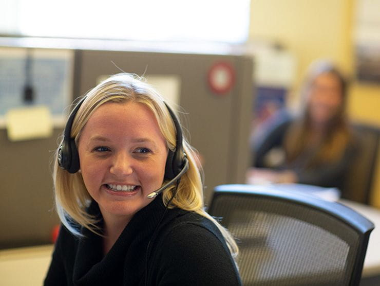 Happy call center employee assisting a customer