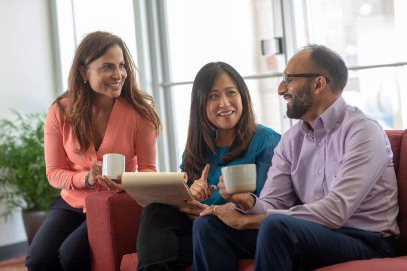 Three diverse co-workers happily collaborating at work