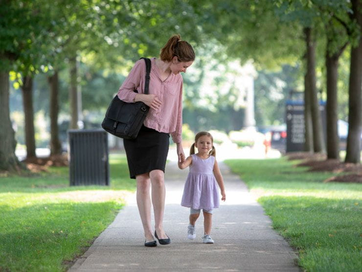 Working mom in leadership walking her daughter home from daycare