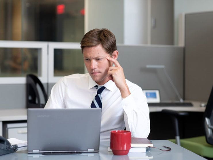 Male employee looking stressed & burned out at his desk