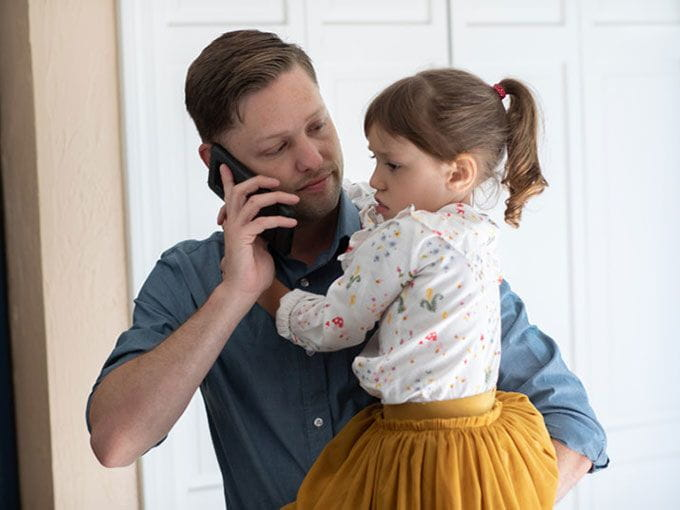 Working dad calling back-up care for his sick daughter