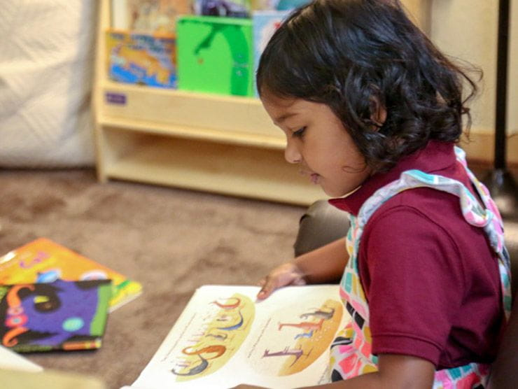 Preschool girl reading at a child care center