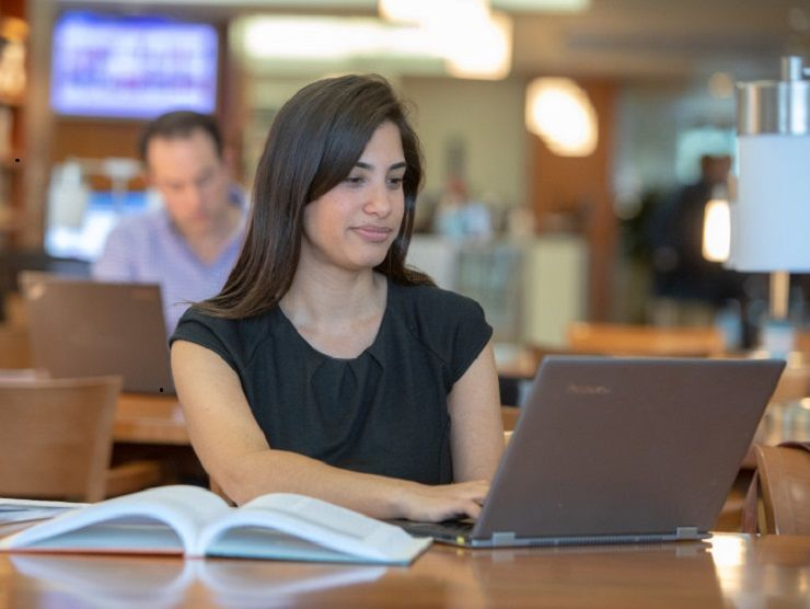 Young female professional studying using her education benefits