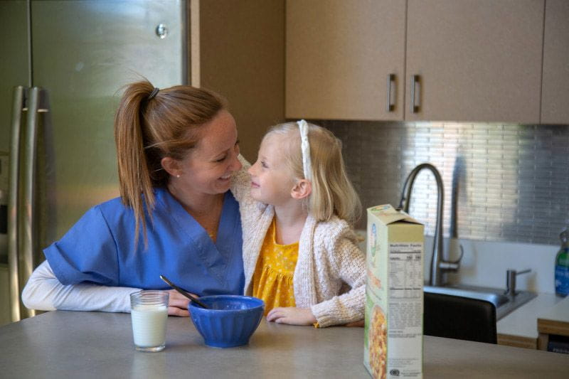Nurse and working mom eating breakfast with her daughter