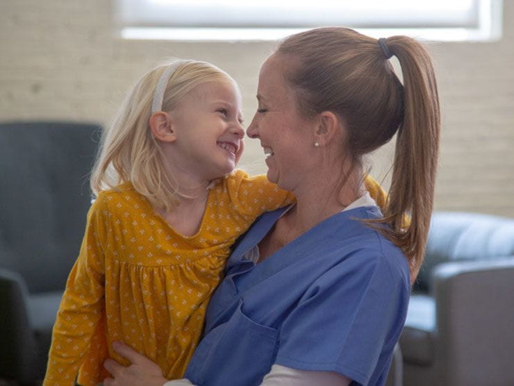 Nurse and working mom hugging her young daughter