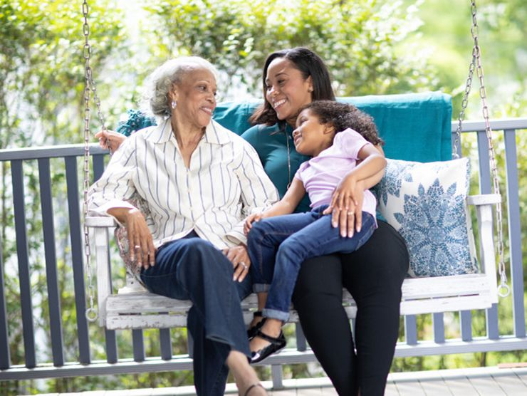 Three generations of women on an outdoor swing
