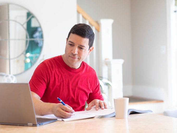 Man studying for online no cost degree at home