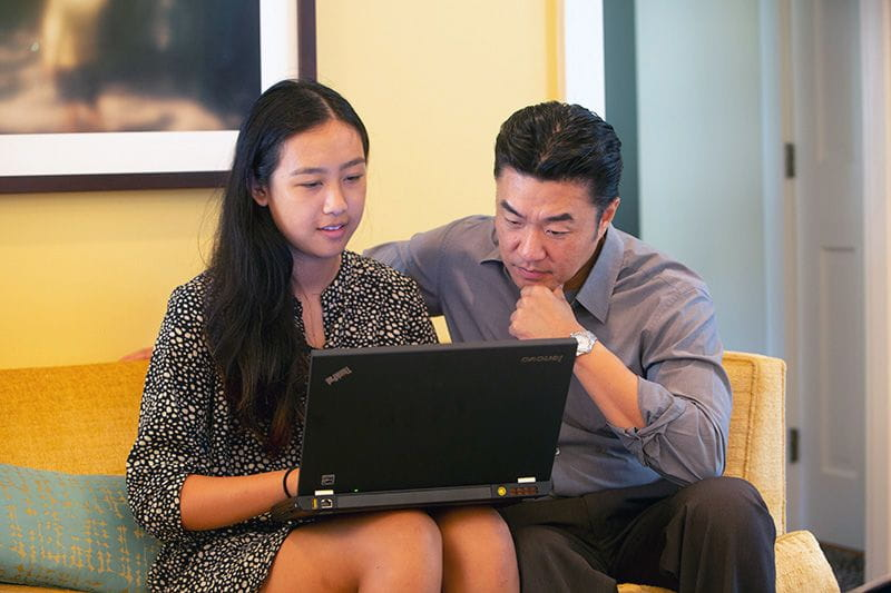 Working dad and teenage daughter looking at college tuition prices