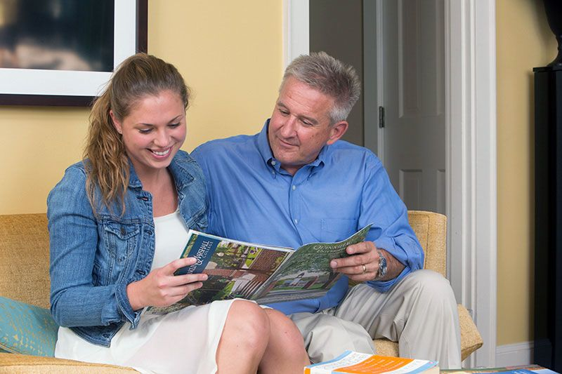 Dad and college-bound daughter looking at a school pamphlet