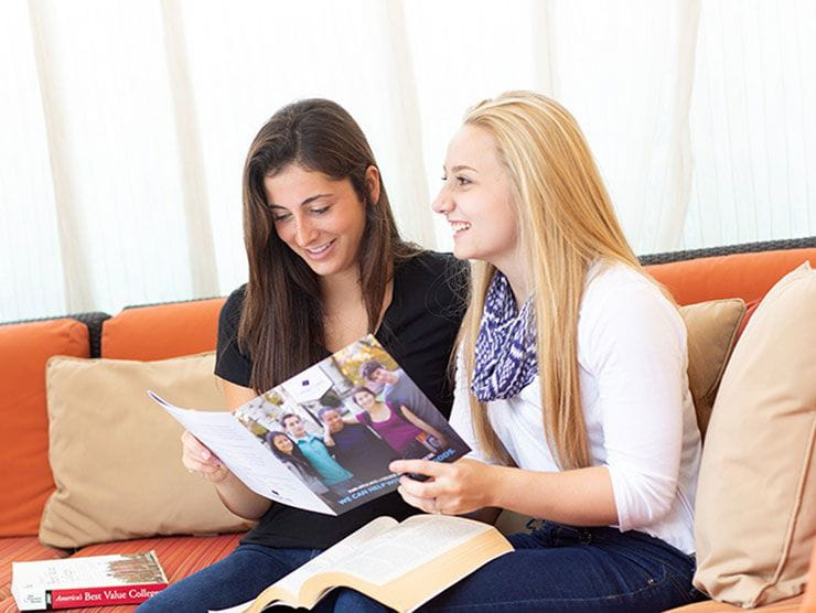 Two high school senior girls researching best value colleges