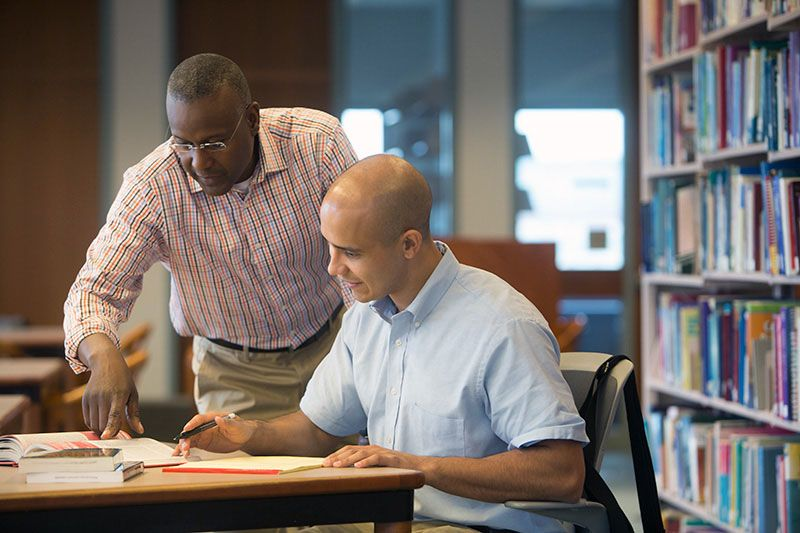 Young man and mentor studying using tuition assistance form his employer