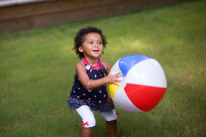 Preschooler playing with a beach ball outside at summer camp