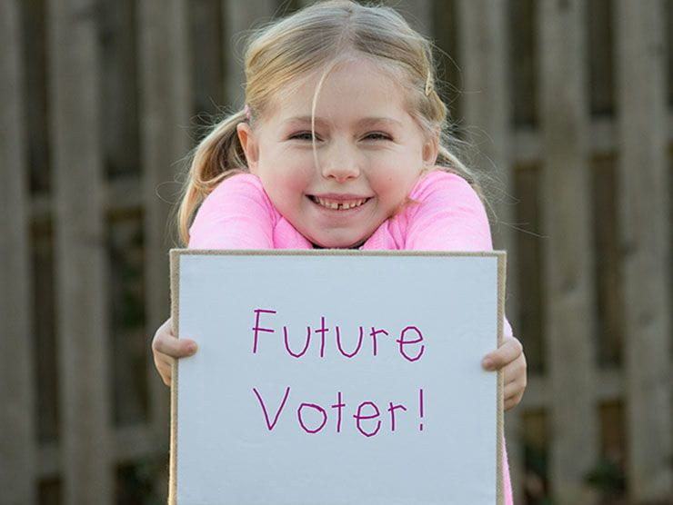 "Little girl holding up a sign that says ""Future Voter"""