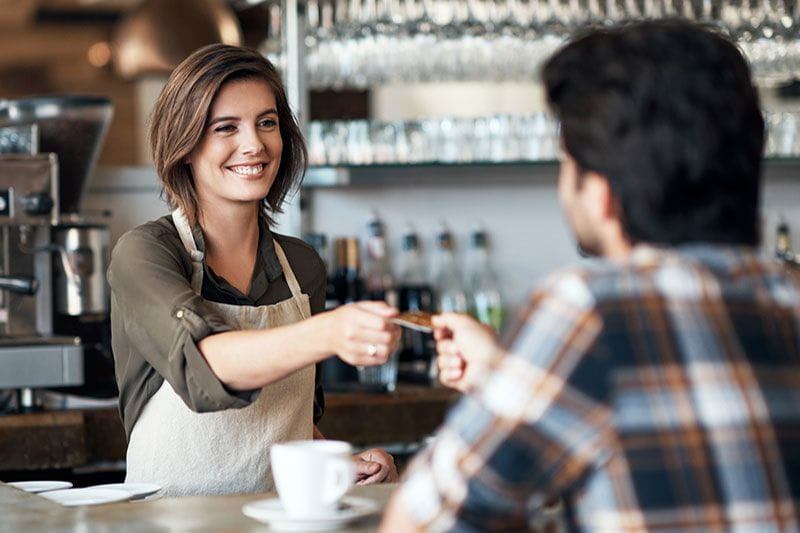 Female barista handing a customer his credit card back