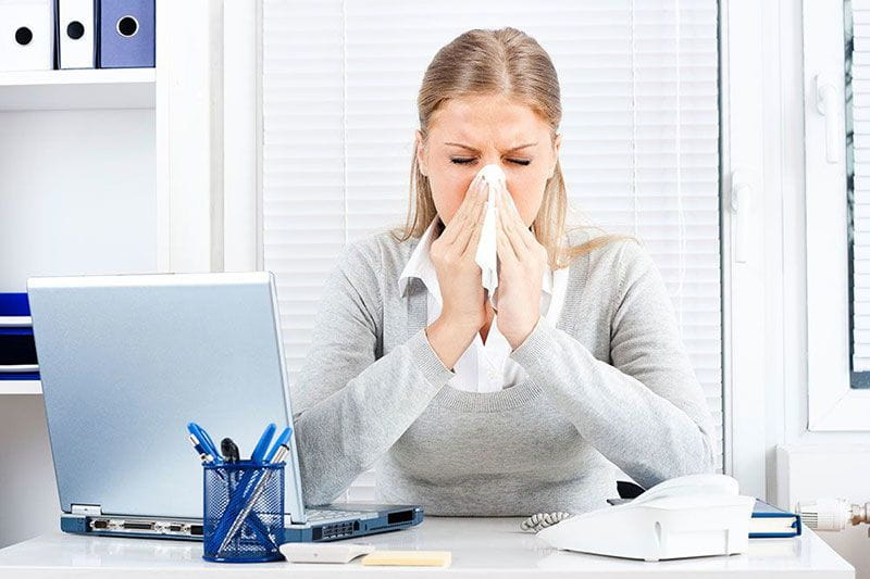 Woman sick with the flu still trying to work
