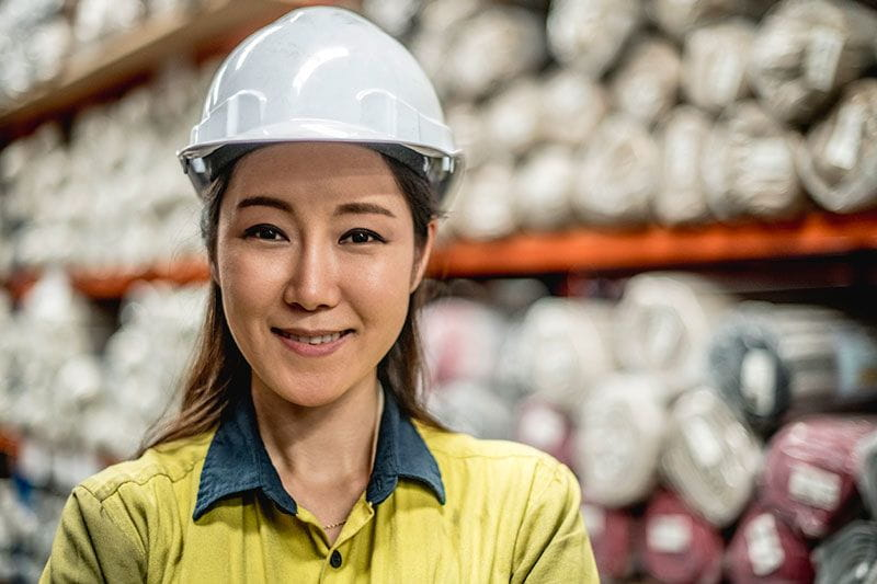 Female manufacturing employee in a hard hat in the warehouse