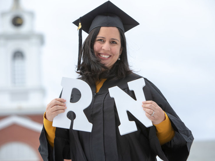 Nurse at her graduation holding the letters 'RN'