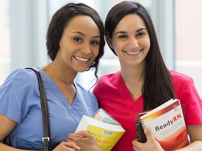 Two female nurses with study books in hand