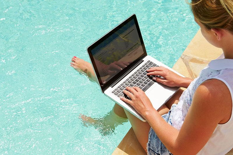 Employee working on her computer at the pool on vacation