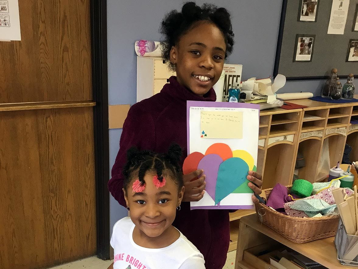 girls at Bright Horizons at Midtown Detroit hold up thank you cards for first responders