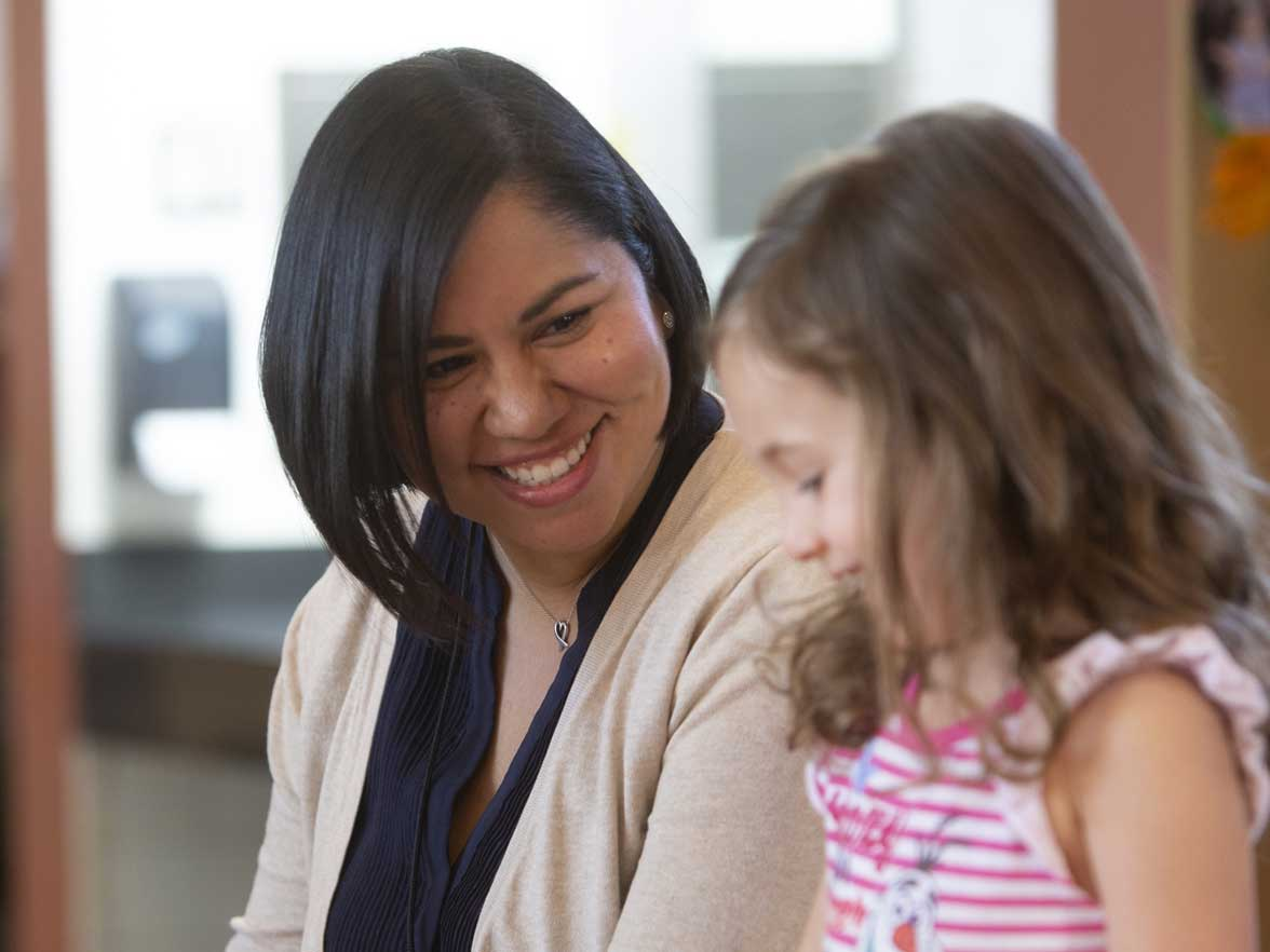 Teacher smiling with a preschool aged girl in a center