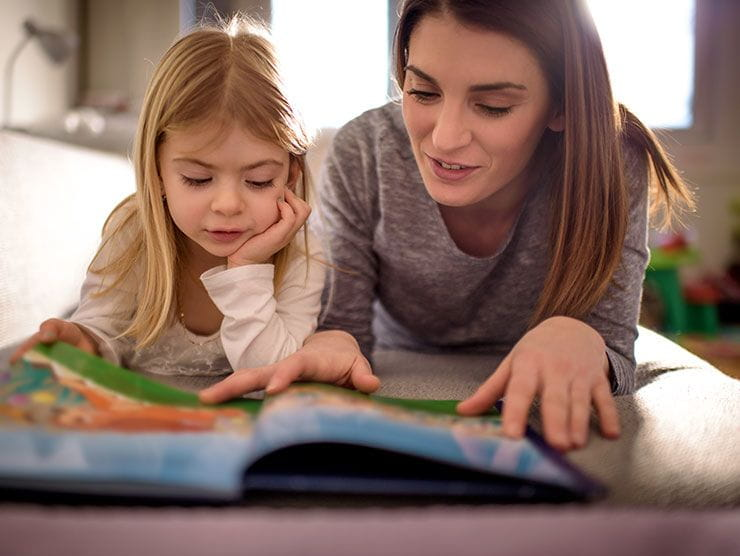 mom reading book to her daughter