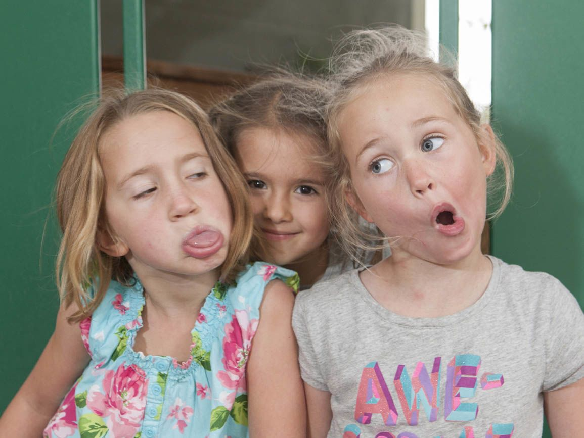 three toddler girls making funny faces