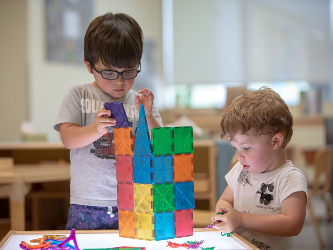 Two preschool boys doing a STEM activity with building squares