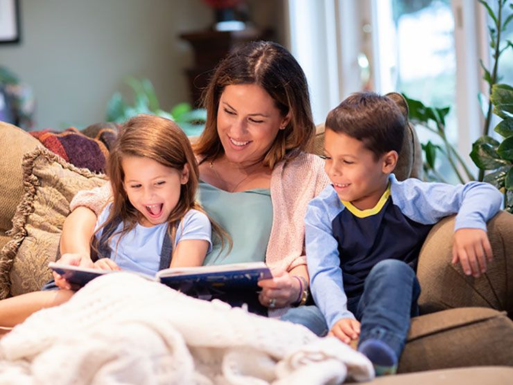 Mom reading with her two kids at home