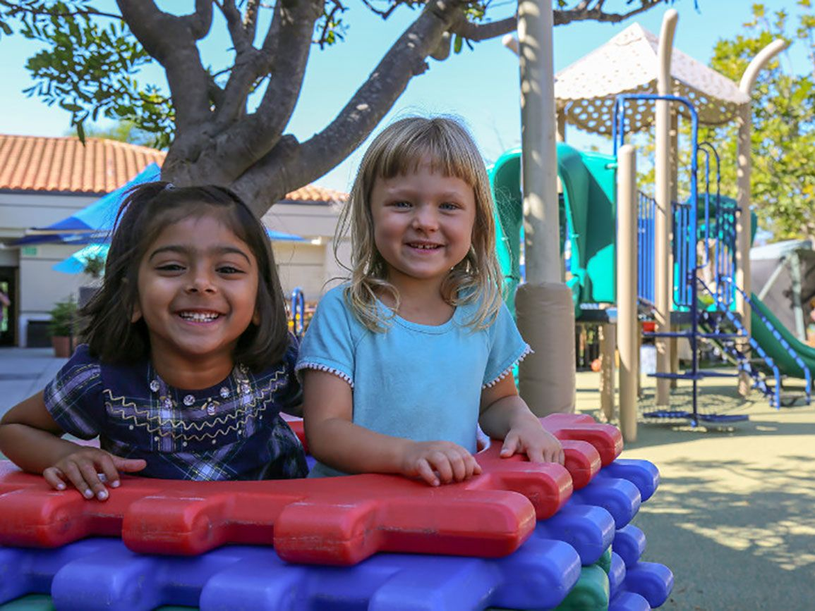 Two preschool girls playing together on the playground