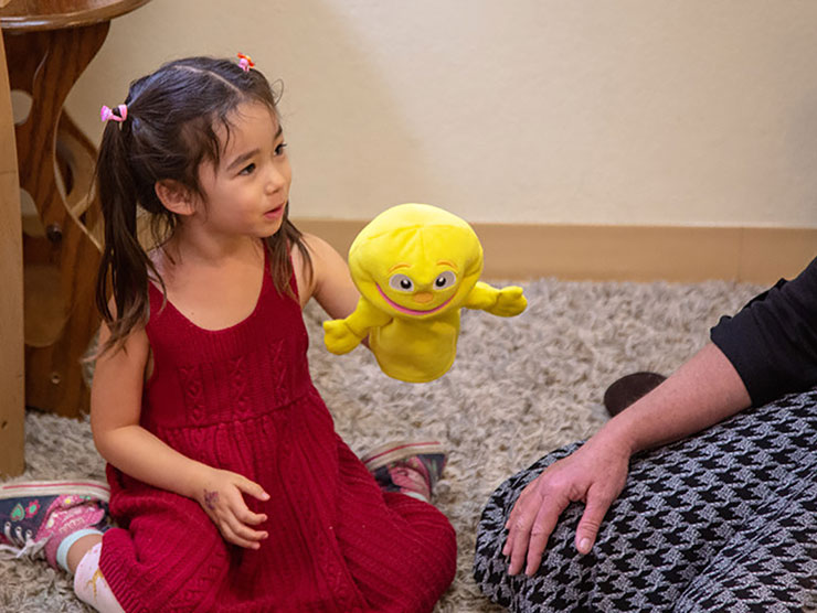 Young girl learning empathy through play with puppets