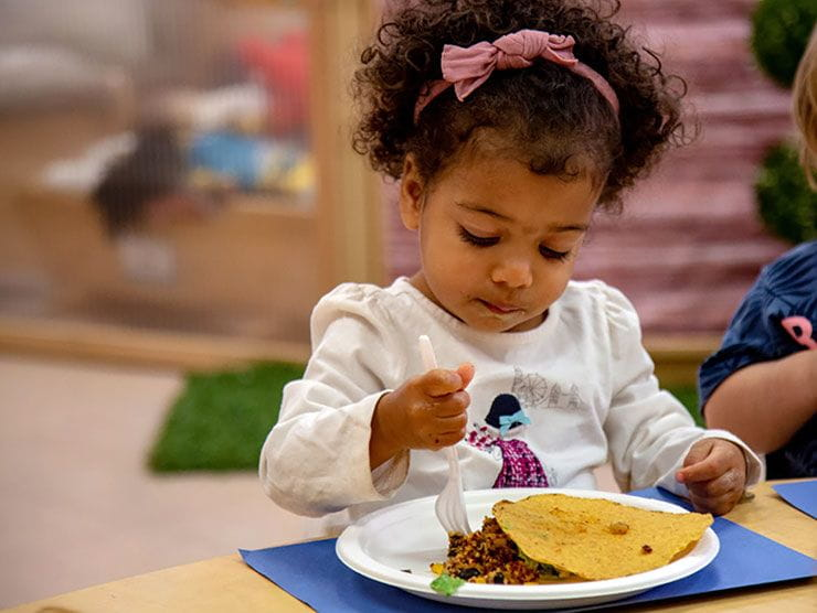 Preschool girl eating a healthy meal at a child care center